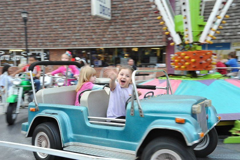 Girl waving from a toy jeep on a ride at the 2012 Fall Festival